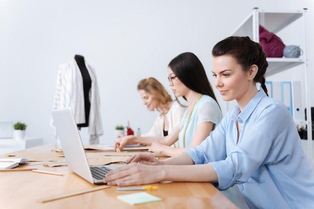 アトリエスタジオのテーブルに並んで座っている3人の魅力的な若い女性は、それぞれが独自のタスクを実行しますが、共通のプロジェクトに取り組んでいます
