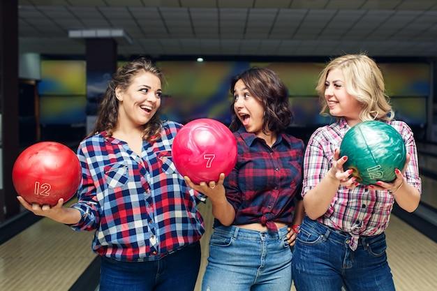 3人の陽気な魅力的なガールフレンドがボウリングのボールを持ってお互いを見ています