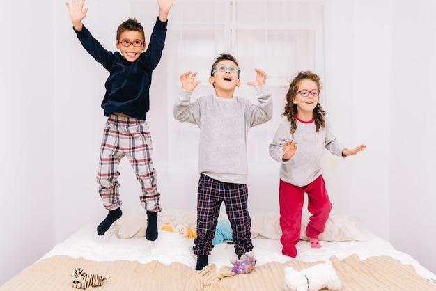 Трое веселых детей в очках прыгают и играют на кровати