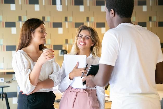 Tre designer allegri che stanno insieme e discutono del lavoro