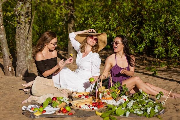 夏のピクニックで3人の陽気なガールフレンド