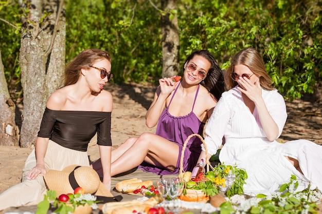 Three cheerful girlfriends at a summer picnic