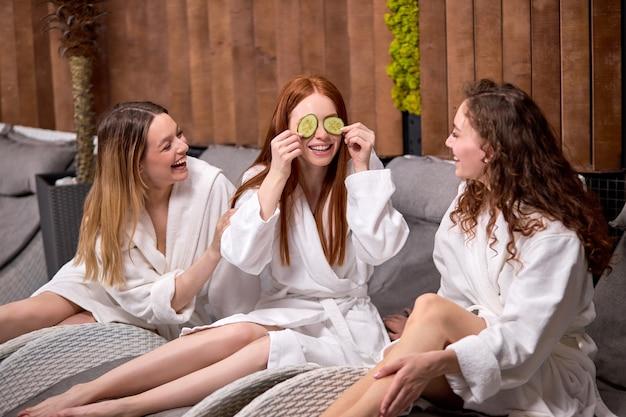 フェイスケアルーチンで新鮮な野菜を使ったきゅうりのスライスを持ったバスローブを着た3人の陽気な女性が楽しんでいる