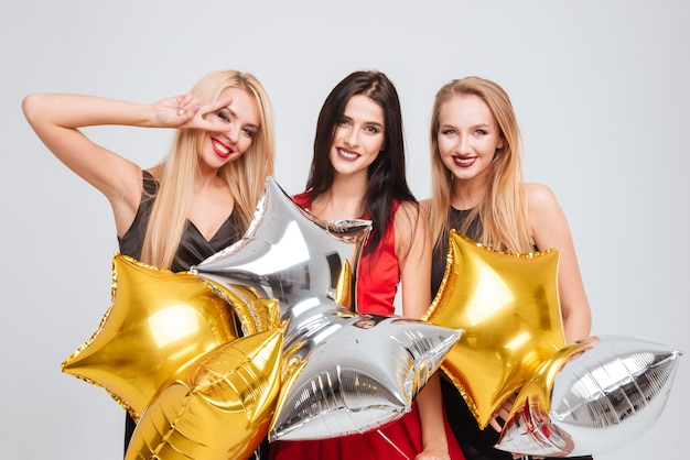 Three cheerful lovely girls holding star shaped balloons over white background