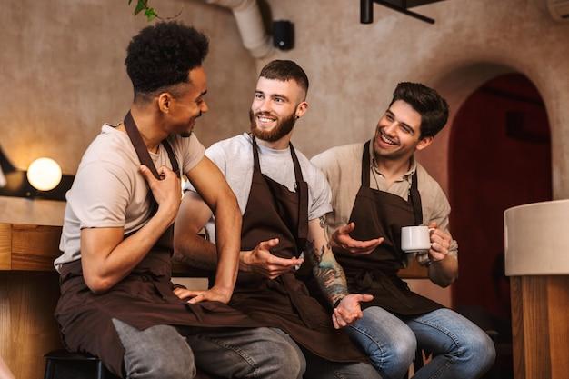 Три веселых мужчин-бариста, стоящих у прилавка в кафе в помещении