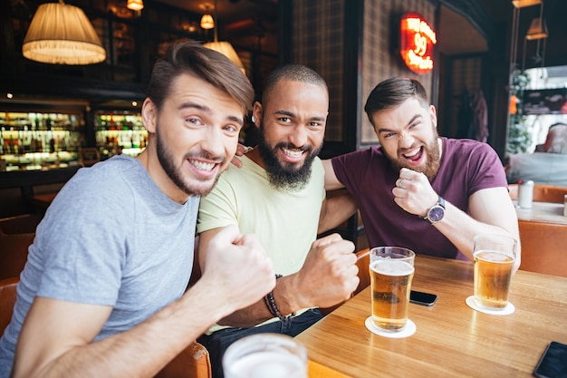Three cheerful male friends sitting at the table in beer pub and looking at front