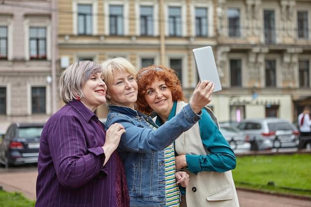 Три веселые зрелые красивые подруги делают селфи на планшетном пк на улице города.