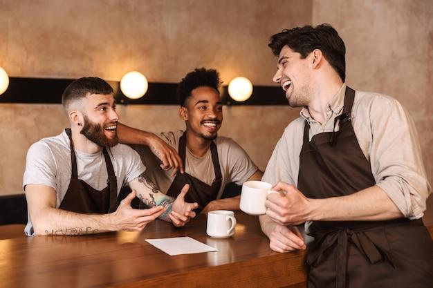 休憩中にコーヒーを飲みながら、喫茶店で3人の陽気な男性バリスタ