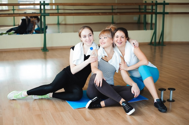 Three cheerful sportswomen laughing and having fun after workout in the gym. cute female take a rest after hard physical activity sporty friends portrait.