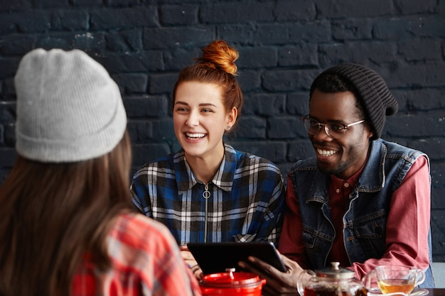 Three cheerful students dining at restaurant, talking to each other and having fun
