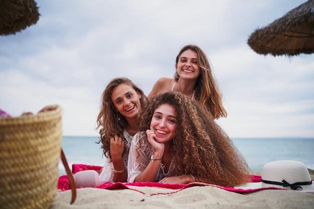 Три веселые женщины отдыхают на красном полотенце на пляже, улыбаясь в камеру