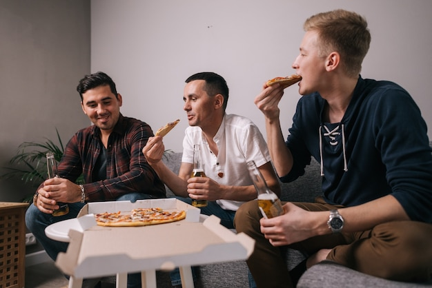테이블에서 피자를 먹는 쾌활한 세 젊은이