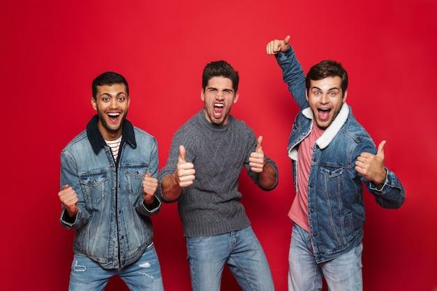 Трое веселых друзей молодых людей стоя изолированно над красной стеной, показывая жест рукой
