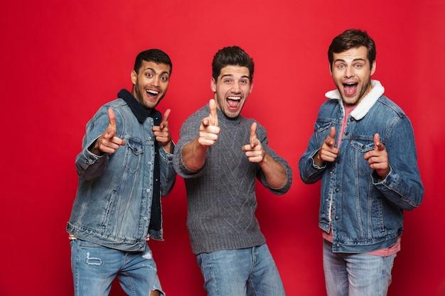 Трое веселых друзей молодых людей стоя изолированно над красной стеной, указывая на камеру
