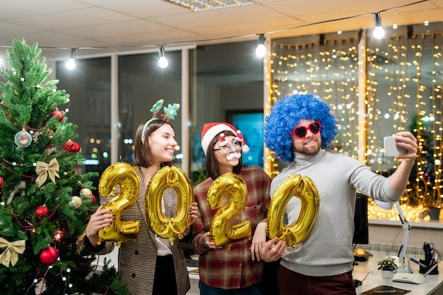 Three cheerful young office managers holding inflatable numbers while making selfie by decorated firtree in office