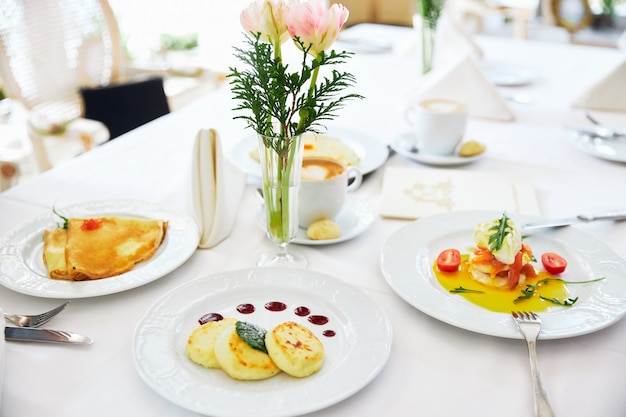 Three cheesecakes and pancakes on a white plate with jam background of a vase with flowers restaurant