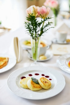 Three cheesecakes on a white plate with jam on the table against the background of a vase with flowe...