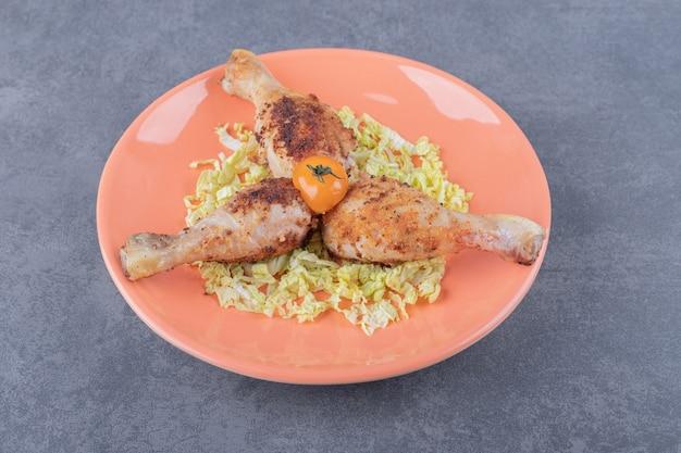 Tre cosce di pollo sul piatto arancione.