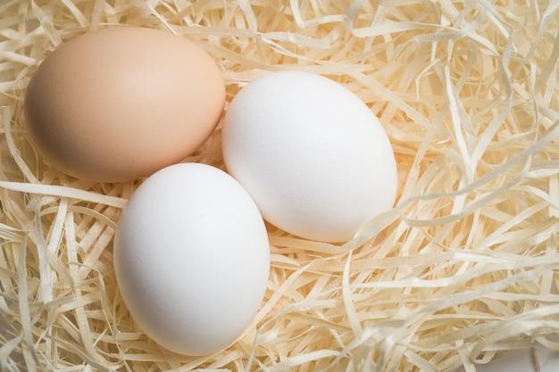 Three chicken eggs lie in a nest of straw, shot