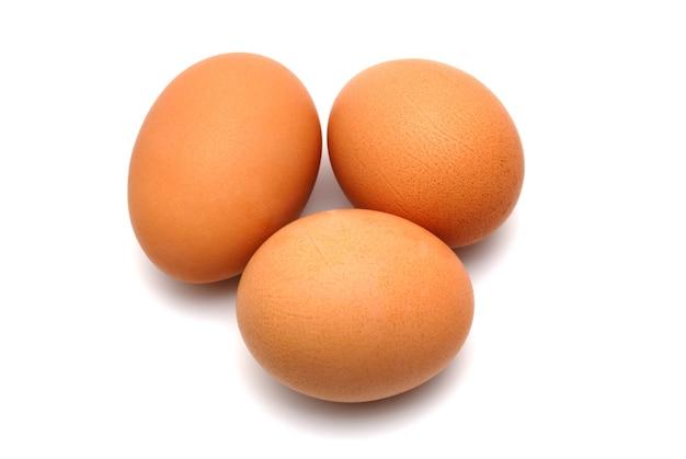 Три куриных яйца на белом фоне крупно