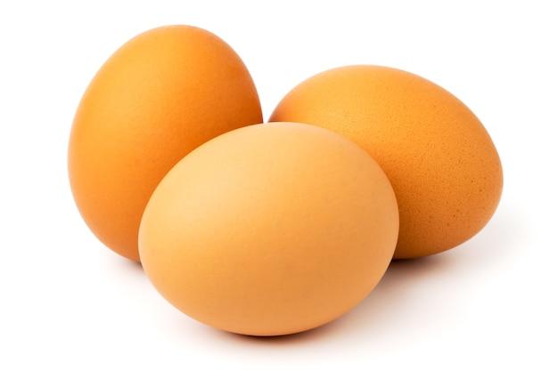 Три куриных яйца на белом, крупным планом.