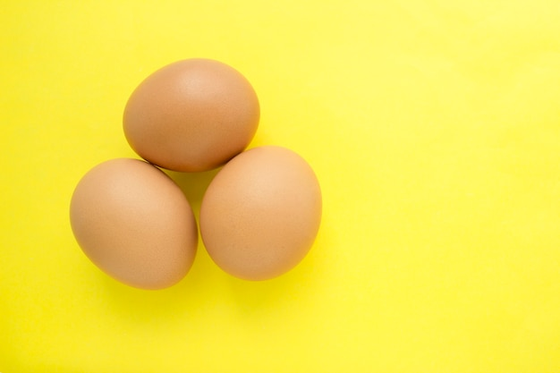 Three chicken eggs on a yellow background