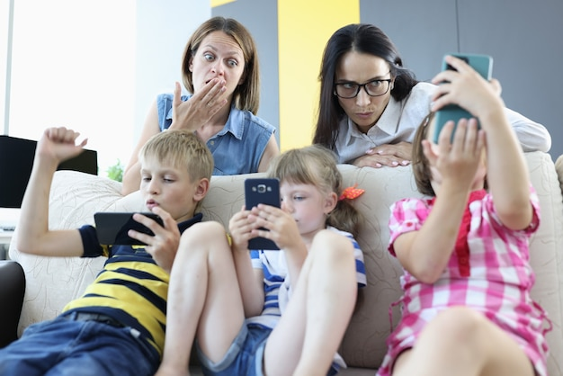 Three children are sitting on the couch with smartphones in their hands, playing online games from back of couch, two women are standing and looking frightened at phone screen.