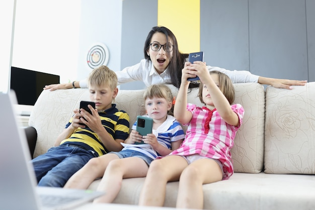 Three children are sitting on couch with smartphones in their hands, playing online games with woman standing behind couch and looking frightened at phone screen.