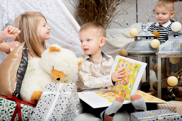 장식 된 집에서 크리스마스 선물 상자 사이에 앉아 세 아이 아이. 메리 크리스마스와 해피 홀리데이!