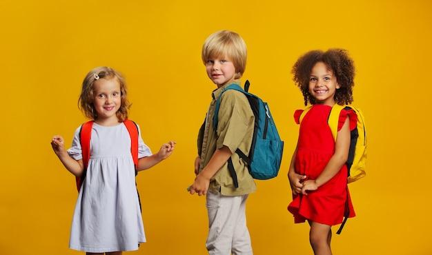 Трое детей студентов разных этнических групп со школьными рюкзаками