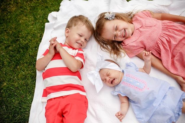 庭の毛布に乗って笑っている3人の子供
