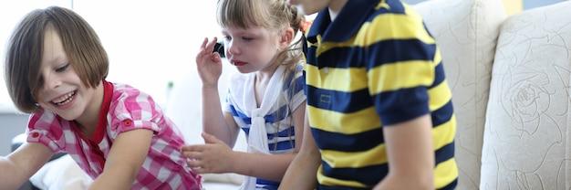 Трое детей играют в настольную игру, одна девочка сидит и плачет