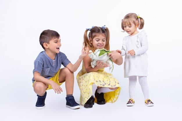 세 아이 자매와 형제가 장난감 흰색 배경에서 옷을 입고 있는 것을 보며 기분 좋게 놀고 있습니다
