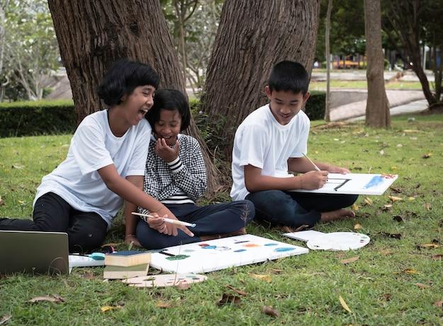 緑の芝生の1階に座っている3人の子供
