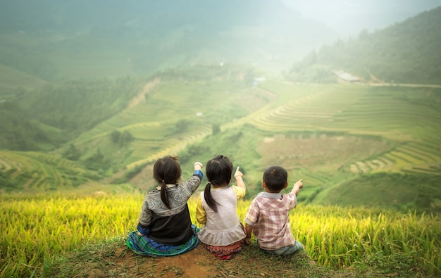 Three children sitting side by side, back view to point to rice paddy fields .