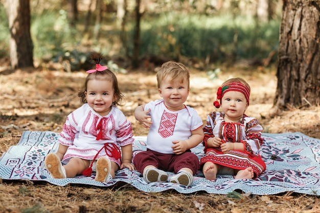 Three children in traditional ukrainian shirts sits on ground in spring forest.