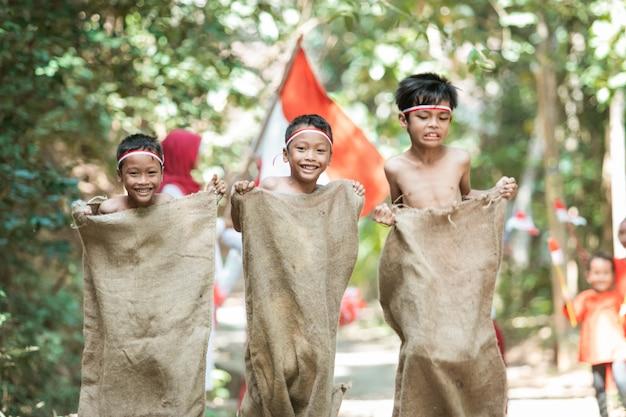 Трое детей пытаются быстро бегать и прыгать в гонке мешков, а друзья их поддерживают