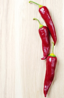 Three chili peppers on wooden table