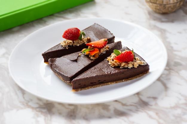 나무 테이블에 세 개의 초콜릿 케이크와 딸기