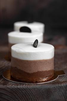 세 개의 초콜릿 케이크는 갈색, 수직, 선택적 초점에 있는 오래된 나무 판자에 닫힙니다