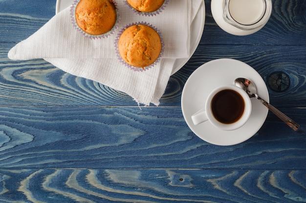 白いプレートと朝食で青い縞模様のテーブルクロスに3つのチョコレートチップマフィン