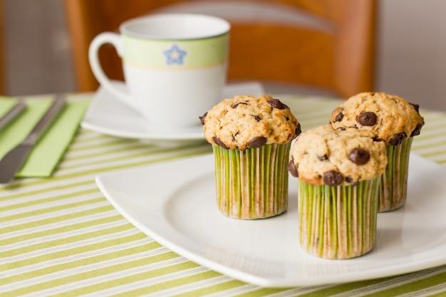 흰색 접시에 초콜릿 칩 머핀 3개와 아침 식사에 녹색 줄무늬 식탁보