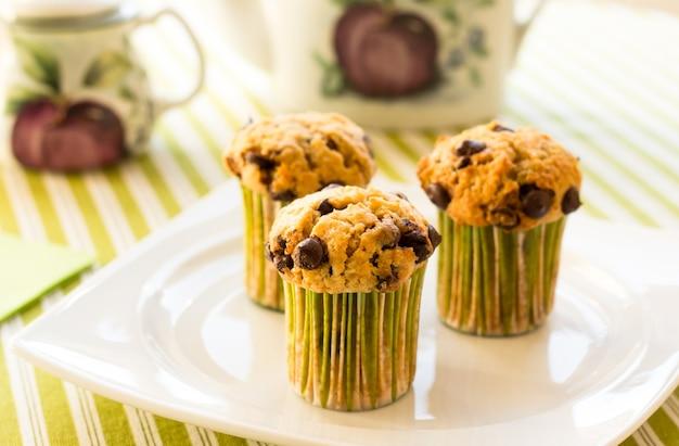 朝食時に白いプレートと緑の縞模様のテーブルクロスに3つのチョコレートチップマフィン