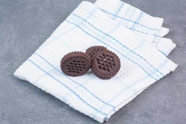 Три шоколадных печенья, лежащих на скатерти.