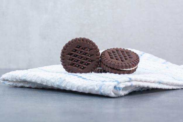 Tre biscotti al cioccolato che si trovano sulla tovaglia.