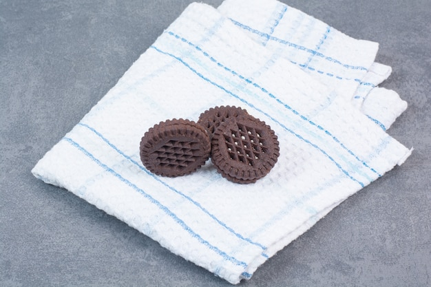 Three chocolate cookies lying on tablecloth.