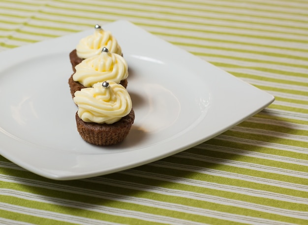 줄무늬가있는 하얀 접시와 패브릭 식탁보에 상단에 은색 뿌리가있는 세 개의 초콜릿 컵 케이크