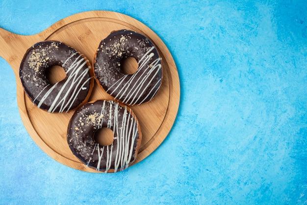 木製プレートと青い背景の上の3つのチョコレートドーナツ。
