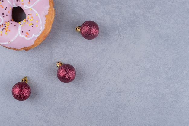 Three christmas baubles and a donut on marble surface