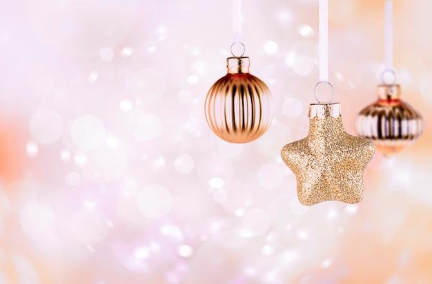 デフォーカスライトピンクの背景に3つのクリスマスの装飾